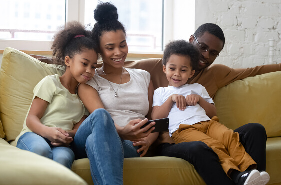 Happy family cuddle close on a couch while watching a video on a phone.
